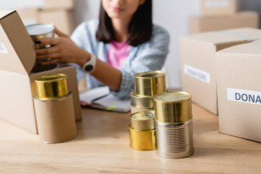 Cropped view of canned food and boxes on table near volunteer in charity center on blurred background stock vector