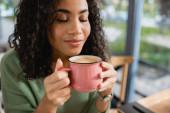 pleased african american woman smelling latte coffee in mug