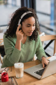 afro-amerikai nő hallgat podcast közelében laptop kávézóban