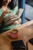 oříznutý pohled na africkou americkou ženu listující stránkami knihy v kavárně