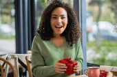 amazed young african american woman holding red christmas gift box in cafe