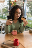 african american woman looking at credit card while holding smartphone in cafe