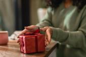 verpacktes Weihnachtsgeschenk bei Afroamerikanerin in Café
