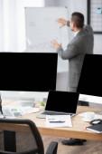laptop és számítógép monitorok üres képernyő közelében kereskedő mutató kézzel flipchart homályos háttér