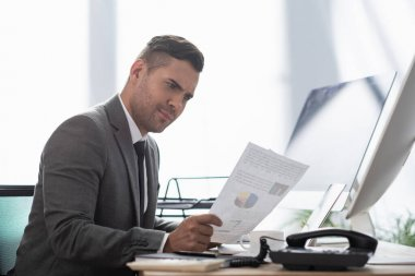 Thoughtful trader looking at paper with infographics near computer monitors stock vector