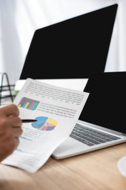 Cropped view of trader pointing with pen at infographics near laptop and monitor with blank screen, blurred foreground stock vector