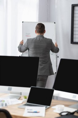 Back view of trader standing near flipchart and monitors with blank screen on blurred foreground stock vector