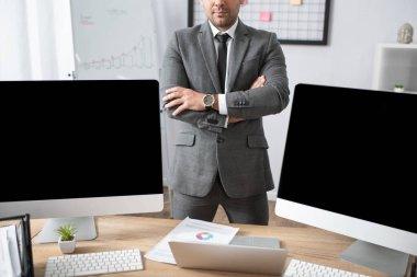 Bilgisayarın ve bilgisayar monitörlerinin yanında çapraz kollu duran tüccar görüntüsü