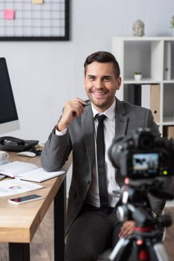Smiling businessman recording video on digital camera, blurred foreground stock vector