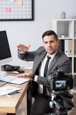 Trader showing amount gesture during video streaming on digital camera, blurred foreground stock vector
