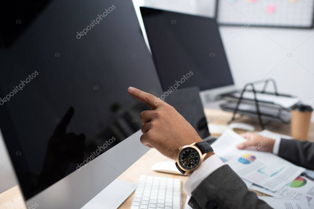 Cropped view of trader in wristwatch pointing at monitor with blank screen stock vector