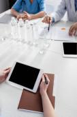 Oříznutý pohled na sestru držící digitální tablet s prázdnou obrazovkou v blízkosti papírové složky a kolegy na rozmazaném pozadí