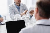 Ausgeschnittene Ansicht des Arztes mit digitalem Tablet in der Nähe von Wasserflaschen und Kollegen im unscharfen Vordergrund