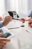 Doctors pointing with finger and pen at brain anatomical model at workplace with devices on blurred foreground