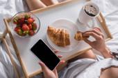 oříznutý pohled na ženu s croissantem, jahodami a kakaem k snídani při držení smartphonu v posteli