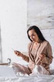 schockierte junge brünette Frau sitzt morgens mit Smartphone, Kreditkarte und Laptop im Bett