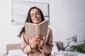 usmívající se mladá brunetka žena sedí v posteli s knihou ráno