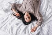 vrchol pohled mladé brunetky žena ve svetru spí v posteli v dopoledních hodinách