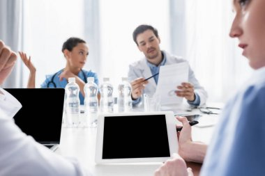 Nurse holding digital tablet with blank screen near doctor on blurred foreground in clinic stock vector