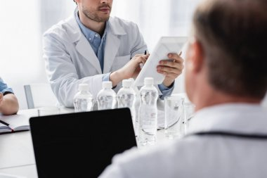 Cropped view of doctor using digital tablet near bottles of water and colleague on blurred foreground stock vector
