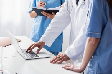 Cropped view of doctor in white coat using laptop near nurses with notebook stock vector
