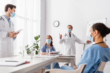 Doctor in medical mask pointing with finger near multiethnic colleagues with papers and digital tablet in clinic stock vector