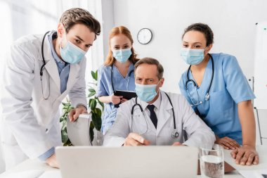 Multiethnic doctors and nurses in medical masks using laptop at workplace in hospital on blurred foreground stock vector