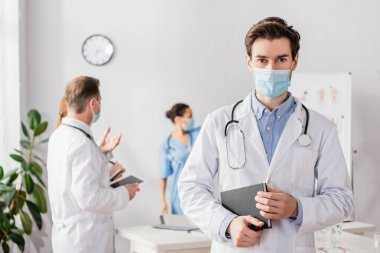 Doctor in medical mask looking at camera while holding notebook with blurred colleagues working on background stock vector