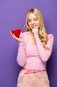 shy blonde young woman holding red heart shaped box on purple background