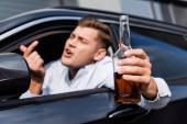 részeg férfi egy üveg alkohollal mutatja, hogy jöjjön ide gesztus, miközben néz ki az autó ablakán, elmosódott előtér