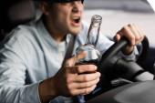 ostříhaný pohled na agresivního, opilého muže s lahví whisky křičící při řízení auta