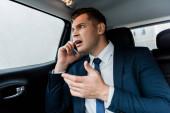 Dühös üzletember beszél okostelefonon a hátsó ülésen az autó
