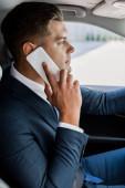Fiatal üzletember beszél okostelefon automatikus homályos háttér