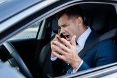 Angry businessman talking on smartphone in car on blurred foreground