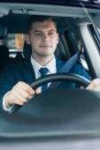 Fiatal üzletember öltönyben autóvezetés elmosódott előtérben