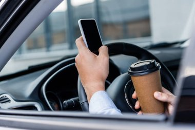 Partial view of man holding coffee to go and chatting on smartphone in car on blurred foreground stock vector