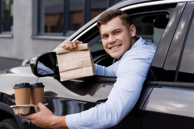 Happy man holding disposable cups and paper bag while sitting in car and looking at camera stock vector