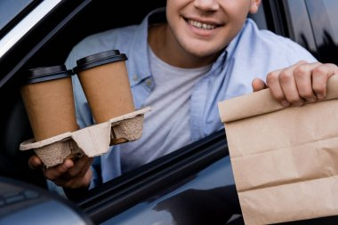Cropped view of smiling man holding paper bag and coffee to go in car, blurred foreground stock vector