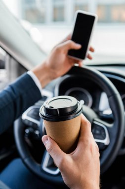 Cropped view of businessman holding coffee to go and smartphone on blurred background in car stock vector