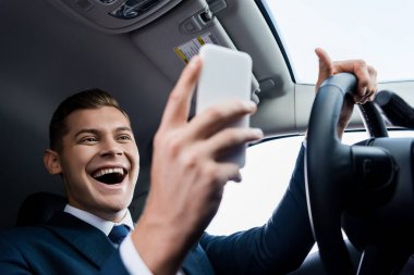 Low angle view of cheerful businessman driving auto and using smartphone on blurred foreground stock vector