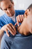 terapeut pracující se zraněným afroamerickým pacientem trpícím bolestí