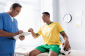 orvos írásban recept közelében sérült afro-amerikai focista mutogatott ujjal a klinikán