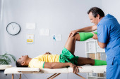 Photo side view of middle aged masseur working with injured african american sportsman in sportswear in clinic