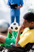 Verärgerter afrikanisch-amerikanischer Sportler im Rollstuhl hält Fußball in der Nähe von Arzt auf verschwommenem Hintergrund