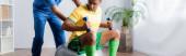 africký americký sportovec cvičí s činkami na fitness míči u fyzioterapeuta, prapor