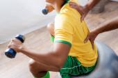 oříznutý pohled na trénink afroamerického sportovce s činkami na fitness míči u fyzioterapeuta