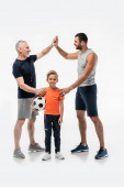 happy boy holding soccer ball and smiling at camera near dad and grandfather giving high five on white