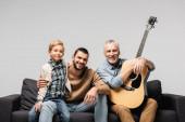 boldog érett férfi akusztikus gitár ül kanapén közel fia és unokája elszigetelt szürke