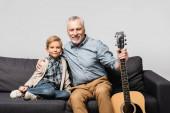 glücklicher Mann mit Akustikgitarre umarmt Enkel, während er isoliert auf dem Sofa auf grau sitzt