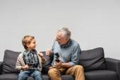 KIEW, UKRAINE - 17. NOVEMBER 2020: glücklicher Großvater und Enkel beim Faustschlag, während sie Steuerknüppel isoliert auf grau halten
